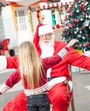 拥抱的圣诞老人和女孩 免版税库存图片