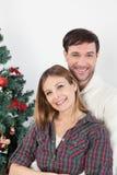 拥抱的夫妇在圣诞树旁边 免版税库存照片