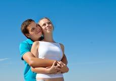 拥抱的夫妇查找天空年轻人 免版税库存照片