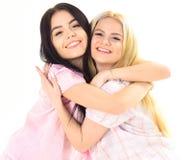 拥抱的女孩紧紧,隔绝在白色背景 姐妹或最好的朋友睡衣的 白肤金发和深色在微笑 库存图片