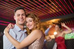 拥抱的微笑的夫妇在酒吧 免版税库存图片