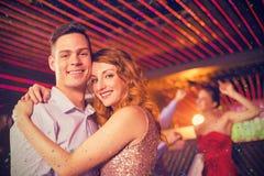 拥抱的微笑的夫妇的综合图象在酒吧 免版税库存照片
