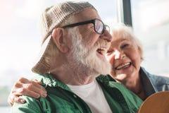 拥抱的微笑的灰发的夫妇 免版税库存照片