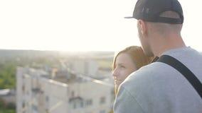拥抱的愉快的年轻美好的时髦的夫妇在房子的屋顶 股票录像