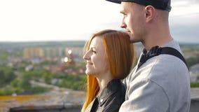 拥抱的愉快的年轻美好的时髦的夫妇在房子的屋顶 影视素材