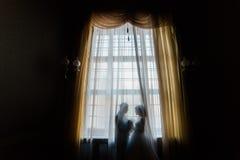 拥抱的新娘和新郎剪影拿着花束反对与帷幕的窗口 免版税库存图片