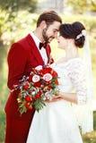 拥抱的新娘和新郎,婚姻的夫妇,深红颜色marsala样式设计 与褐红的蝶形领结,白色礼服的衣服 免版税库存照片