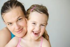 拥抱的母亲和的女儿画象,微笑 免版税图库摄影