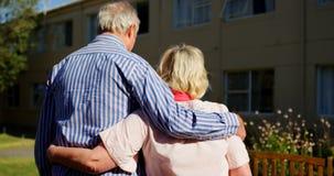 拥抱的活跃白种人资深夫妇背面图在老人院4k庭院里  股票视频