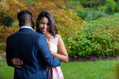 拥抱的浪漫年轻夫妇在五颜六色的秋天树下 免版税库存照片