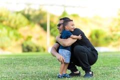 拥抱的父亲和的儿子户外 免版税库存图片