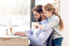 拥抱的父亲和的女儿,当有胡子的人与膝上型计算机一起使用时 库存图片