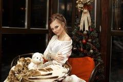 拥抱的美丽的白肤金发的女孩坐的放松与在沙发的温暖的毯子在圣诞树和黑暗的窗口附近 免版税库存图片