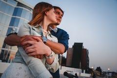 拥抱看日出天空夏时的夫妇在城市,都市背景 免版税库存图片