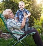 拥抱祖母的小孙子坐在她的胳膊 家庭假日户外 免版税库存图片
