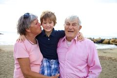 拥抱祖父母的愉快的孩子在夏天 免版税库存照片