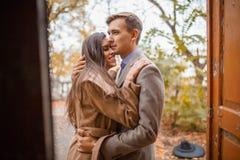 拥抱站立的一对爱恋的夫妇在门外面在秋天公园 免版税库存图片