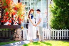 拥抱站立的愉快和年轻人怀孕的夫妇在每ot旁边 图库摄影