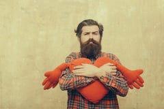 拥抱红色心脏形状玩具用手的哀伤的有胡子的人 免版税库存照片