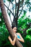 拥抱结构树的亚裔女孩 免版税库存图片
