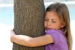 拥抱结构树的女孩 库存图片