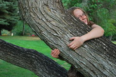 拥抱结构树的女孩 图库摄影