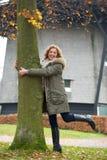 拥抱结构树的妇女 免版税库存照片