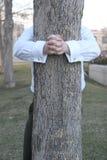 拥抱结构树的生意人 免版税库存照片