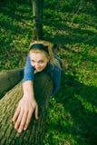 拥抱结构树的白肤金发的女孩 免版税库存照片