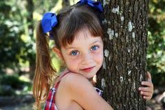 拥抱结构树的逗人喜爱的女孩 免版税库存图片