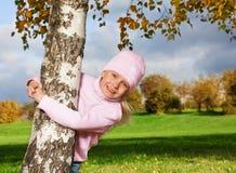 拥抱结构树的逗人喜爱的小女孩 库存照片