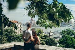拥抱美好的爱恋的夫妇的后面看法画象,当享受布达佩斯的时匈牙利迷人的看法  免版税库存照片