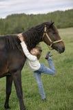 拥抱美好的horse& x27的逗人喜爱的女孩; s脖子和看照相机 生活方式画象 免版税库存照片