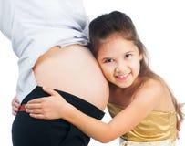 拥抱腹部的小女孩 免版税库存图片