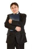 拥抱膝上型计算机现代微笑的生意人 免版税库存照片