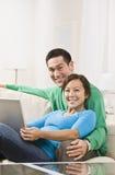 拥抱膝上型计算机的夫妇 库存照片