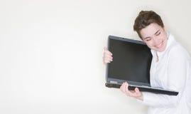 拥抱膝上型计算机的女实业家 免版税库存照片