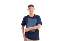 拥抱膝上型计算机的少年男孩 免版税图库摄影