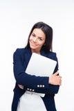 拥抱膝上型计算机的微笑的女实业家 库存图片