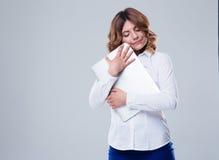 拥抱膝上型计算机的逗人喜爱的女实业家 免版税库存图片