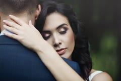 拥抱英俊的新郎与的一个美丽,愉快的新娘的特写镜头 免版税库存图片
