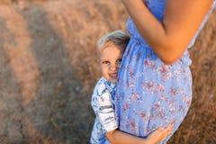 拥抱被弄脏的自然本底的一个愉快的矮小的儿子的特写镜头一个嫩妈妈 童年,家庭观念 库存图片