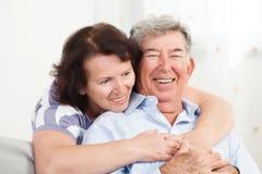 拥抱资深的夫妇微笑和 免版税库存图片