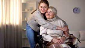 拥抱轮椅、家庭爱和关心的孙女微笑的老妇人 库存照片