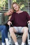 拥抱轮椅的妇女年轻人 免版税库存照片