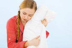 拥抱软的枕头的少妇佩带的睡衣 库存图片