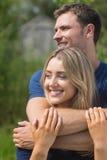 拥抱逗人喜爱的夫妇微笑和 免版税库存图片