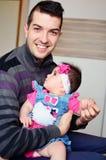 拥抱逗人喜爱的女婴的年轻人 免版税库存照片