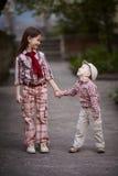 拥抱逗人喜爱的姐妹的男孩和查寻 免版税库存照片