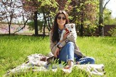 拥抱逗人喜爱的起重器罗素狗小狗的可爱的少妇画象在公园,绿色草坪,叶子背景 行家女性 免版税库存图片
